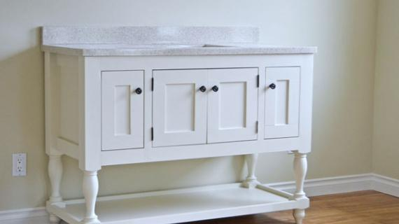white farmhouse style bathroom vanity with turned legs and open bottom shelf