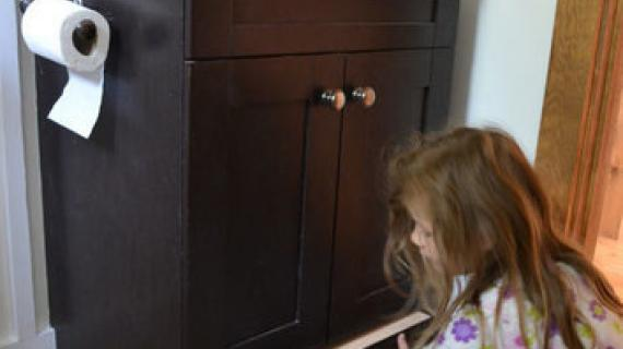 bathroom vanity with little girl pulling out hidden step drawer